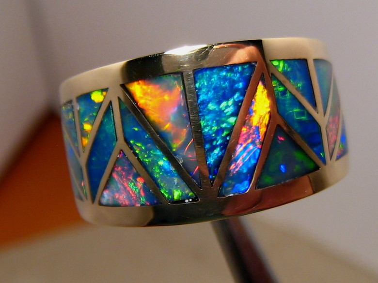 An inlaid opal ring photo without any editing shows reflections, dark areas on the gold and blemishes